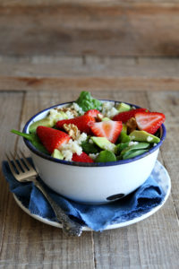Salad in a bowl with spinach, strawberries, goat cheese and walnuts