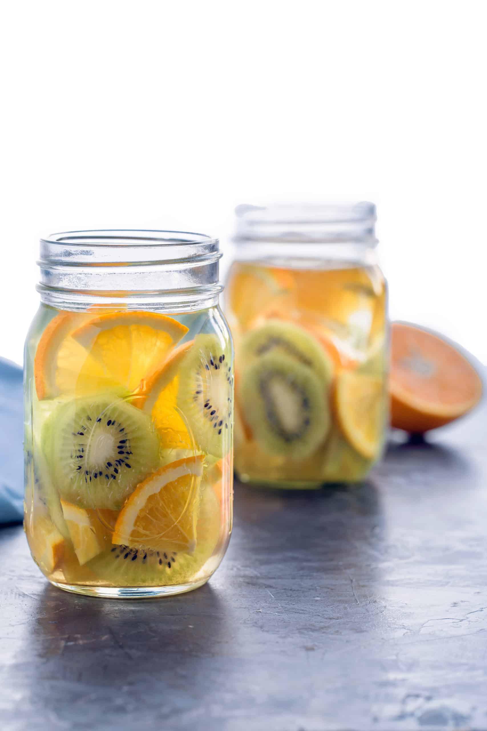 2 mason jars with slices of orange and kiwi